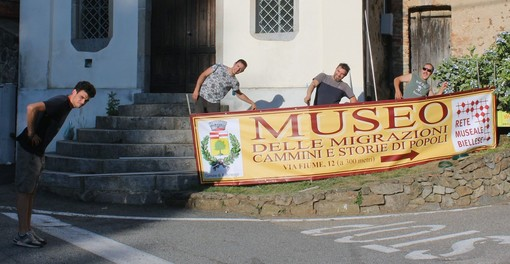 Nell'immagine, ragazzi di Pettinengo (Pro Loco e Alpini) ritratti mentre posizionano striscione del Museo delle Migrazioni all'ingresso del paese; locandina